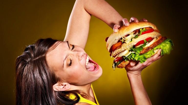 девушка собирается съесть огромный гамбургер, нездоровое питание