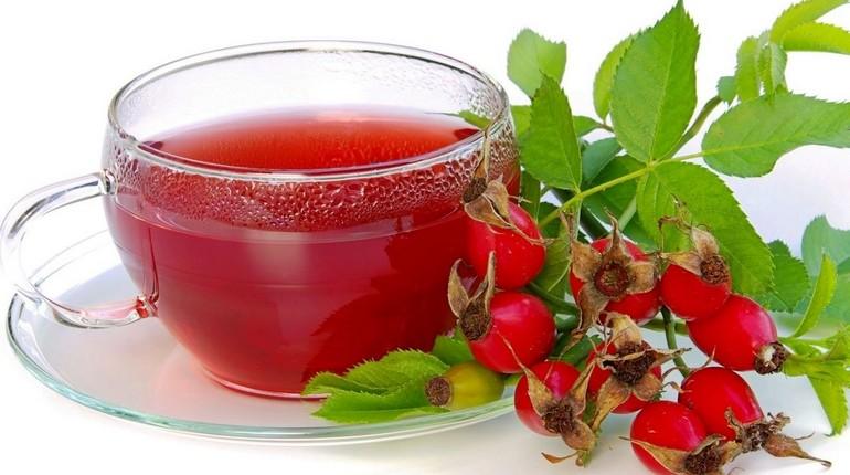 чашка чая с шиповником, чаща и ягоды на столе
