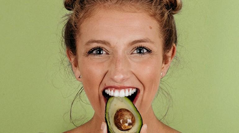 девушка кусает авокадо, питание для позитива и здоровья