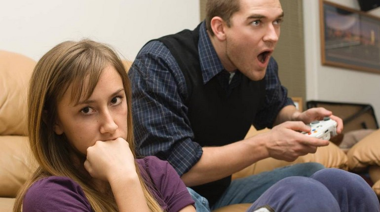 парень увлечен компьютерной игрой, девушка сидит рядом с парнем и скучает а он увлечен игрой