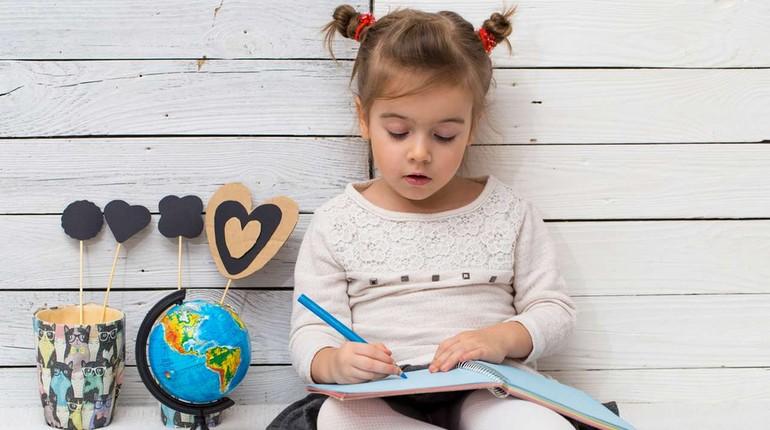 девочка что то пишет в блокноте, девчушка рисует, ребенок готов идти в школу