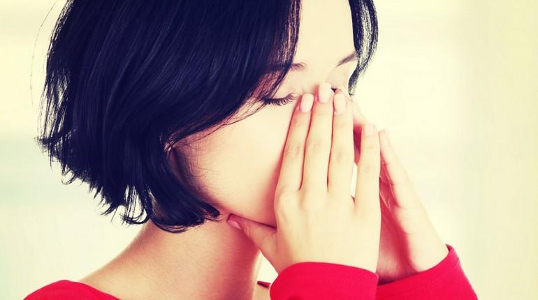 девушка держится за переносицу, проблемы с носом