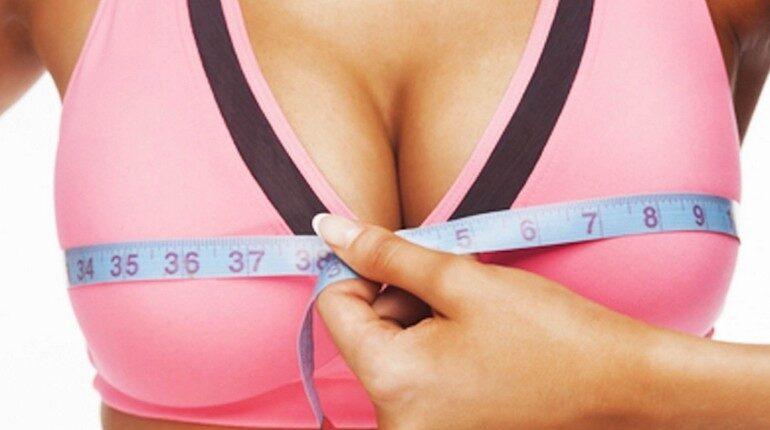 измерение объема груди, увеличение груди, девушка измеряет сантиметровой лентой свою грудь