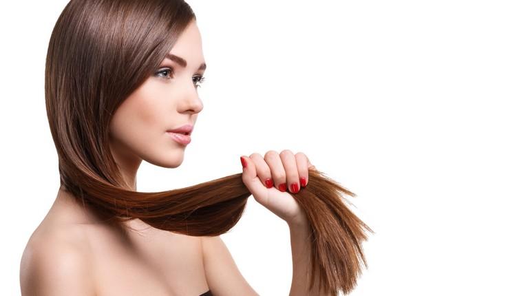 у девушки красивые здоровые волосы, девушка держит в руке свои волосы