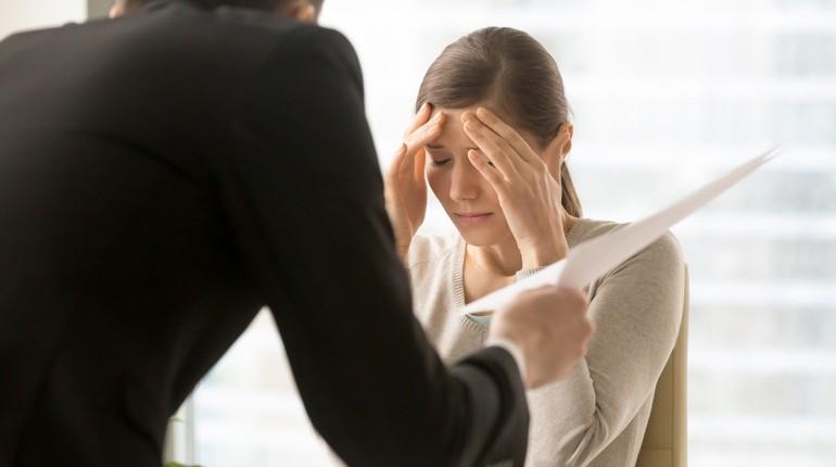 девушка выслушивает нарекания шефа, девушка держит руки возле головы