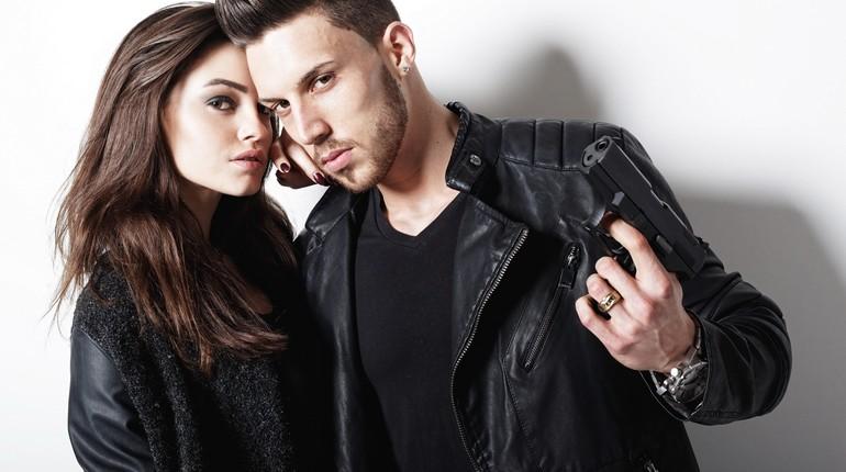 парень стоит с девушкой и держит в руках пистолет, парочка