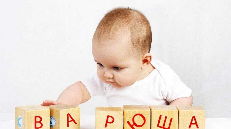 малышка играет кубиками, младенец складывает кубики