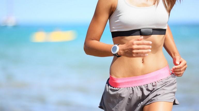 девушка на пробежке, спортсменка ежит вдоль берега моря