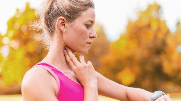 девушка измеряет пульс на шее