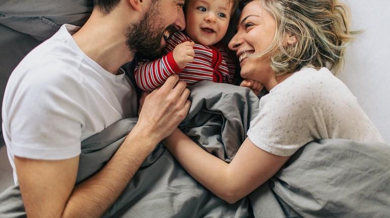 счастливая семья с ребенком, малыш в постели между родителями