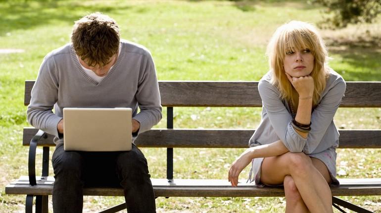 парочка сидит порознь на скамейке, ссора, парень в ноутбуке а девушка в сторонке