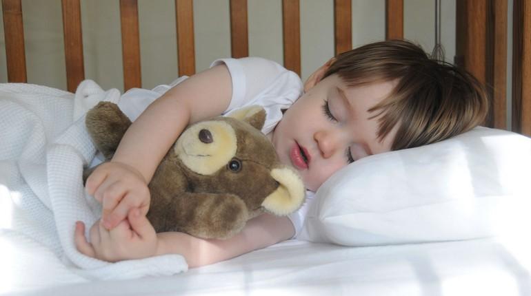 ребенок спит в своей постели, мальчик спит в обнимку с мишкой