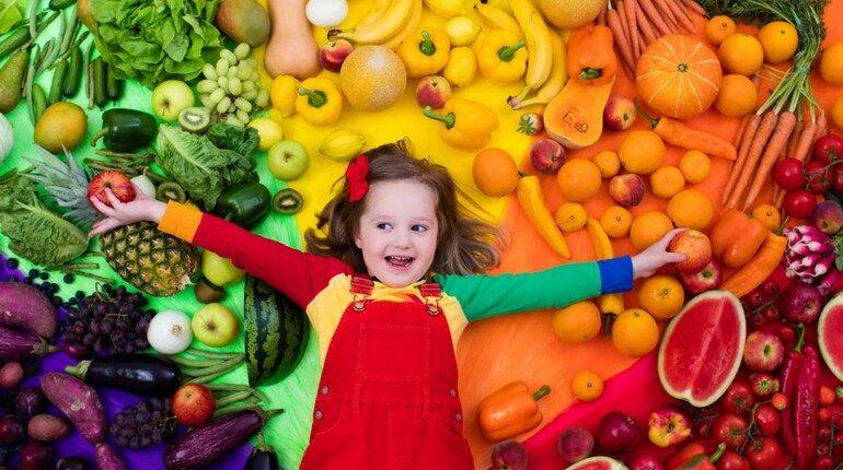ребенок на фоне витаминов, девочка на фоне фруктов и овощей