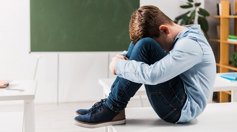 мальчик сидит на полу и спрятал голову в колени, у ребенка депрессия