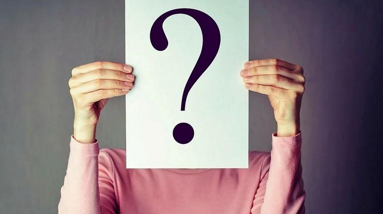 девушка держит лист со знаком вопроса, вопросительный знак в руках девушки