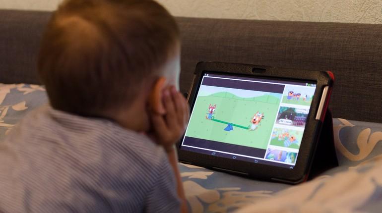 мальчик смотрит что то в планшете, ребенок увлечен планшетом