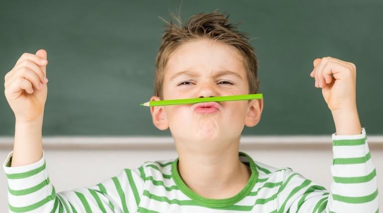 мальчик держит карандаш носом и губами, ребенок балуется