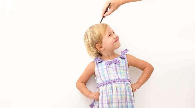 девочке измеряют рост, девочка стоит возле стенки