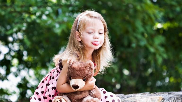 девочка с медвежонком, девочка высунула язык