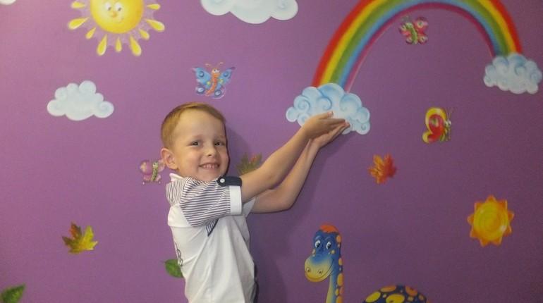 мальчик держит радугу, мальчик на фоне обоев с радугой