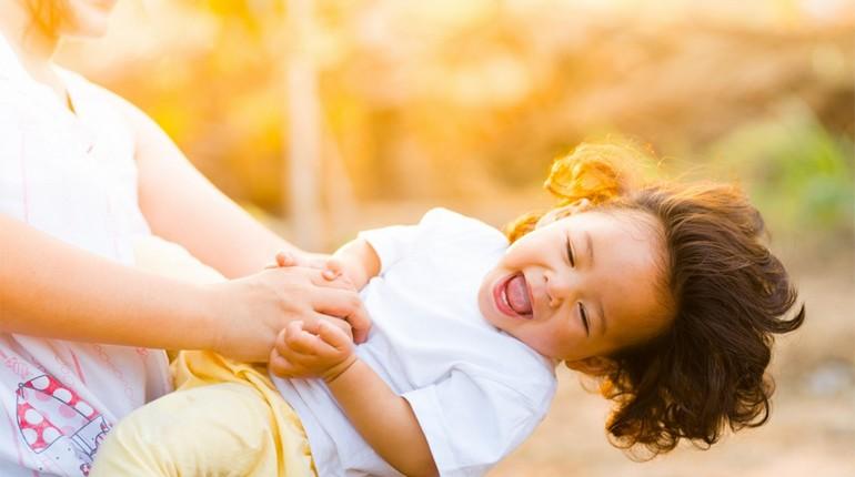 ребенок играется со взрослым, девочка хохочет