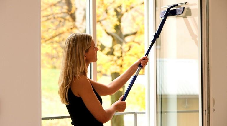 девушка моет окно, уборка дома