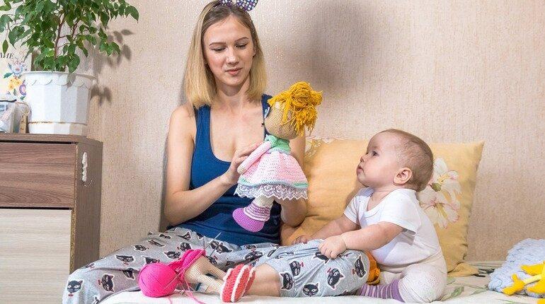 девушка делает руками игрушки и малыш смотрит на маму