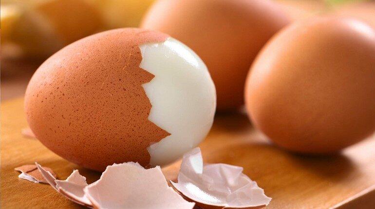 вареные яйца, одно яйцо наполовину очищено