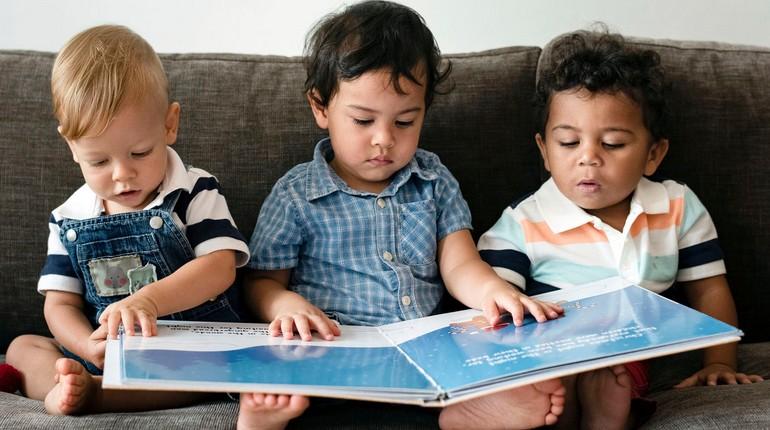 дети разных национальностей, три мальчика рассматривают книжку