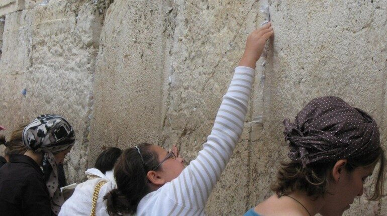 девушка кладет записку у стены плача, иерусалим, паломники в Иерусалиме