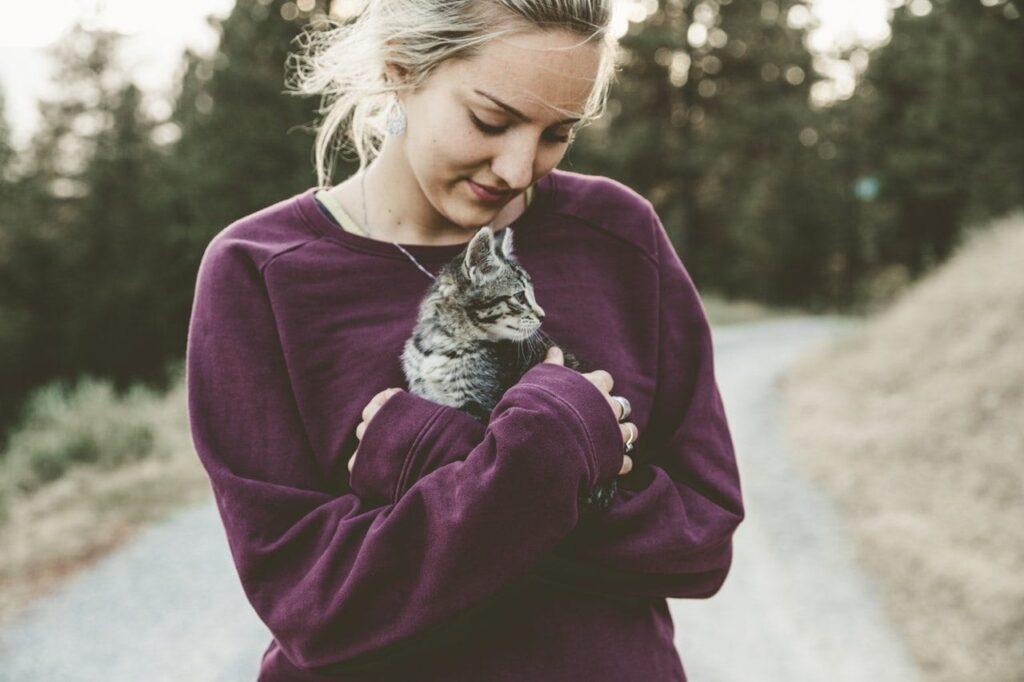 девушка держит котенка, трогательная забота о котенке