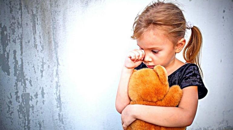 девочка обнимает мишку и плачет, грусть ребенка, лучший друг игрушка
