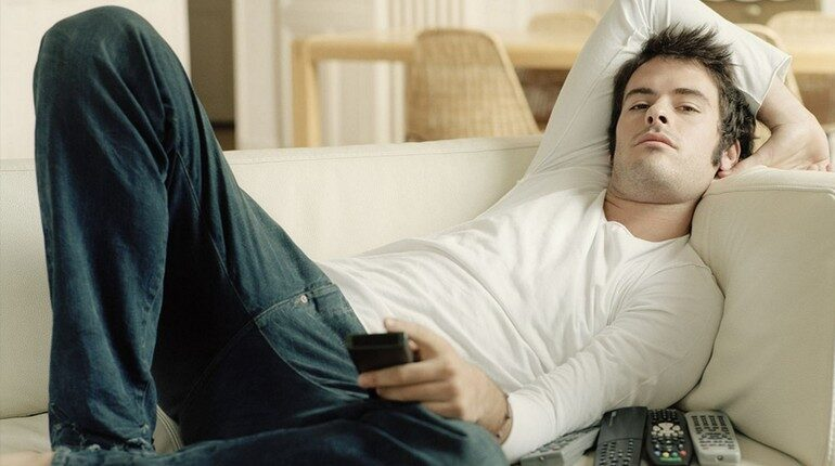 парень лежит на диване, парень с пультом от телевизора, парень отдыхает