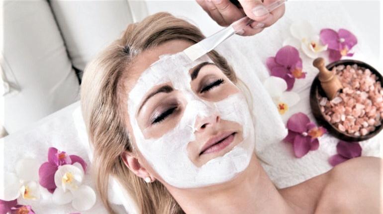 девушка с маской на лице, девушка в салоне, косметические процедуры на лице, белая маска на лице у девушки