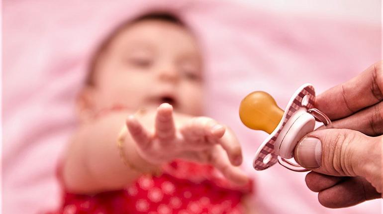 ребенок и пустышка, соска и детская рука