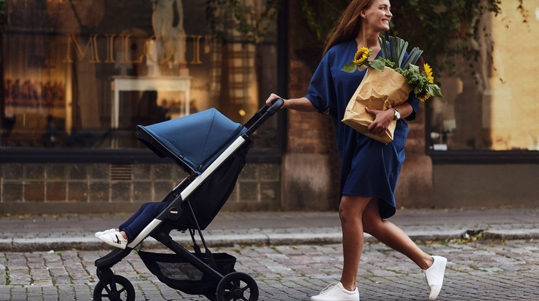 девушка с коляской и покупками, на улице с коляской