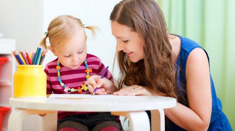 девушка занимается с ребенком, маленькая девочка занимается с няней