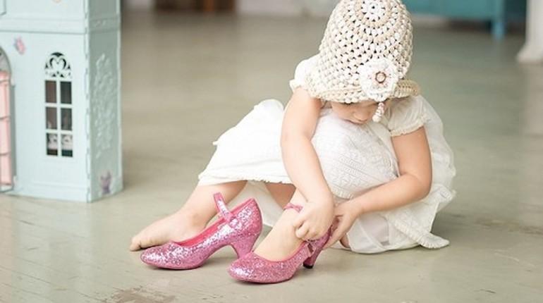 маленькая девочка одевает туфли взрослых, ребенок надевает мамины туфли