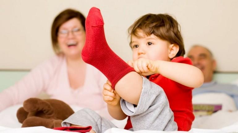 ребенок натягивает носок, мама смеется и ребенок сам одевается