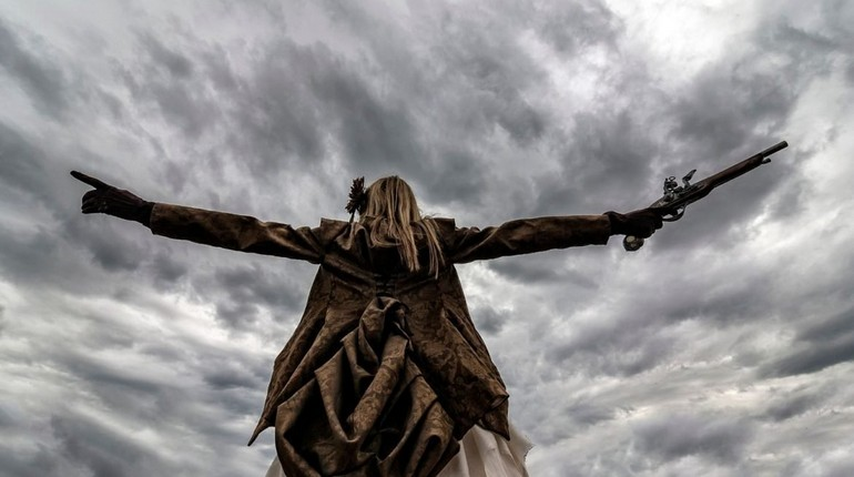 девушка расставила руки на фоне серого неба, общение с небесами