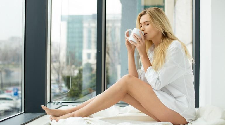 девушка пьет чай из кружки, девушка сидит на подоконнике