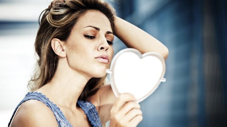 девушка смотрит в зеркальце, разглядывает себя в зеркале