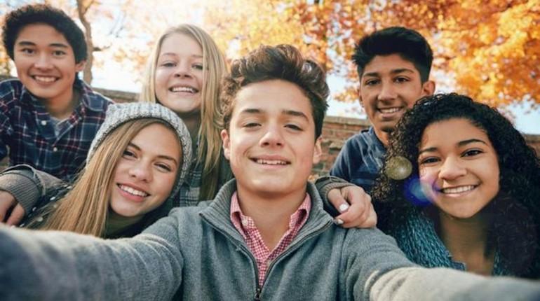 мальчик стоит в центре других подростков, ребята делают селфи, позитивные подростки