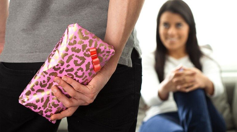 парень делает подарок девушке, приятный сюрприз, девушка улыбается не зная о подарке