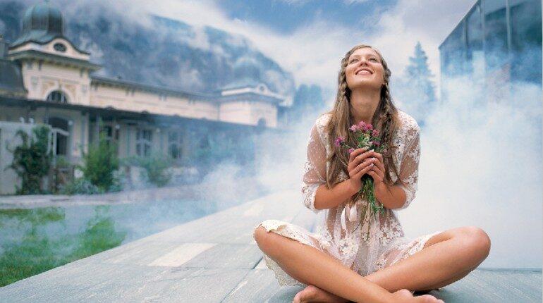 девушка счастлива и испытывает чувство благодарности, девушка сидит на фоне неба и прижимает к себе букет цветов