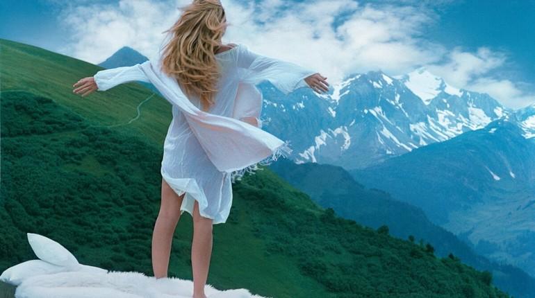 девушка стоит спиной к камере раскинув руки, девушка стоит в горах