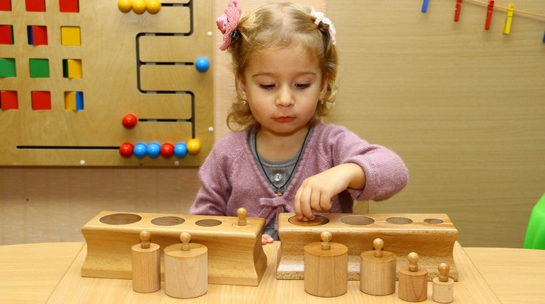 девочка играет деревянными игрушками, игрушки по методике монтессори