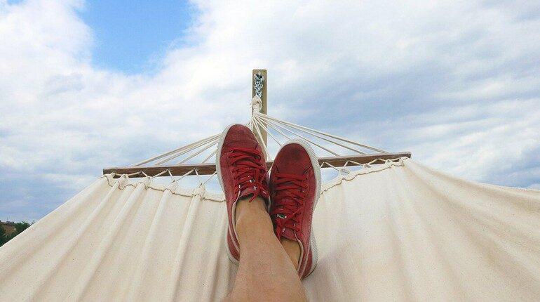 человек лежит в гамаке и смотрит на небо, ноги человека который лежит в гамаке