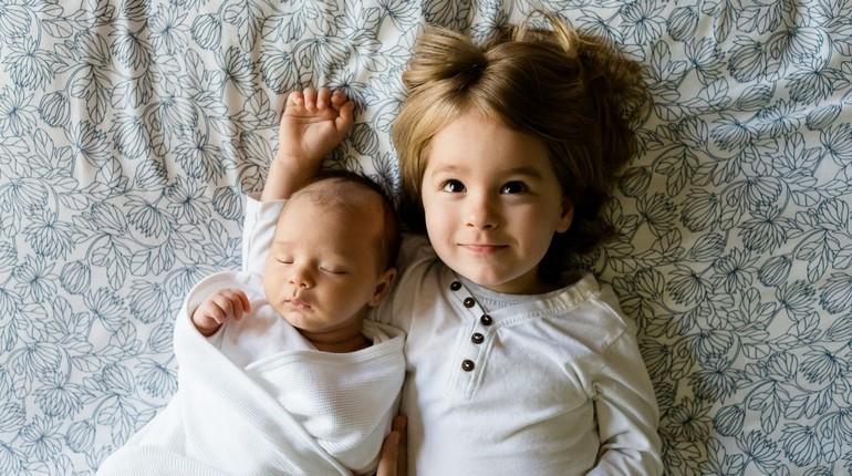 девочка счастлива с новорожденным младенцем, братик или сестричка