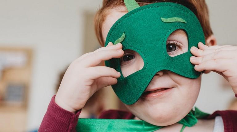 мальчик одел маску на лицо, ребенок одевает карнавальную маску